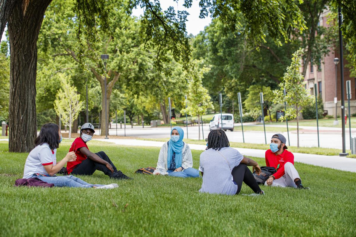 Students wearing masks chatting with physical distancing and face coverings on the Nebraska campus